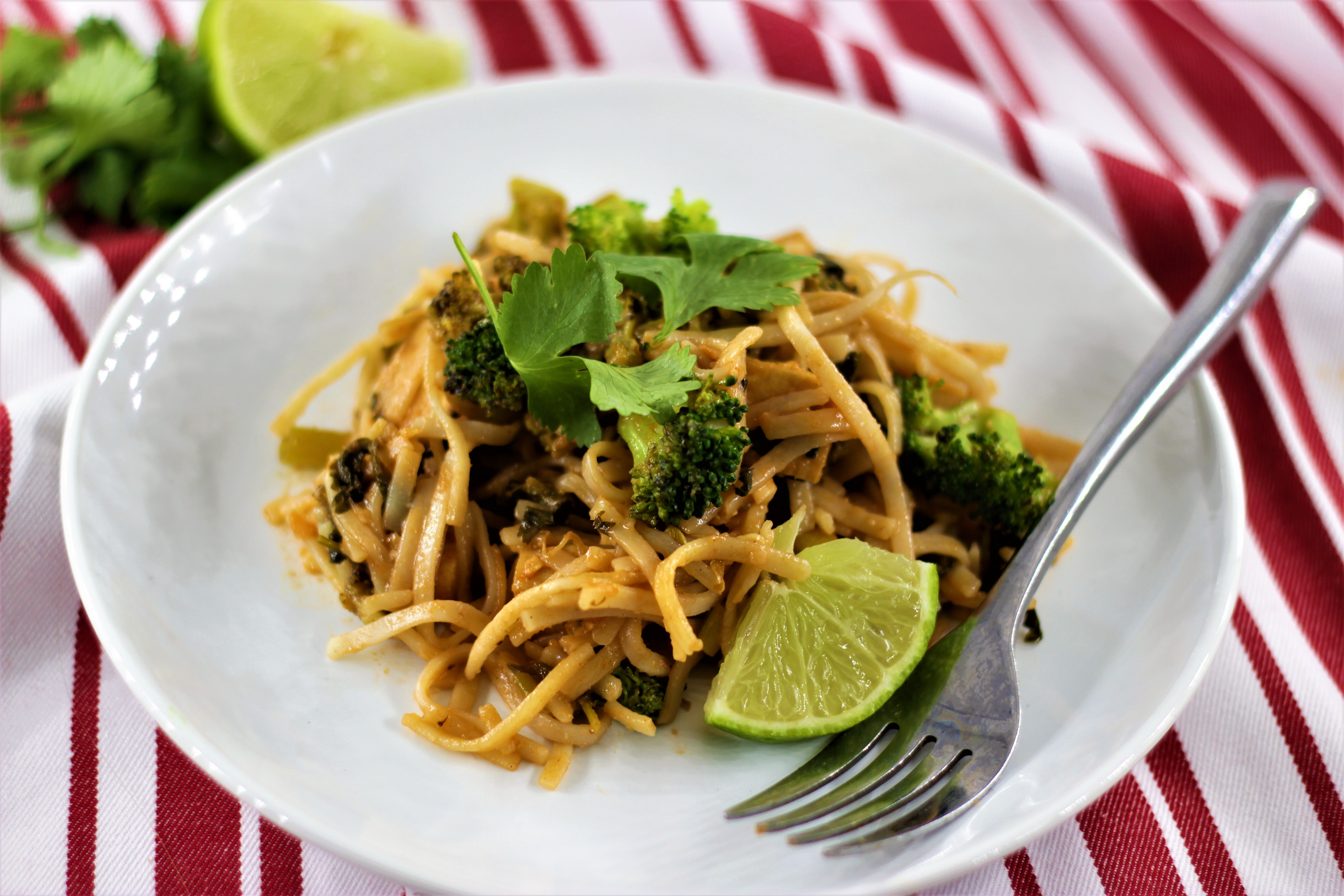 Tofu Pad Thai with broccoli on a white plate with a fork and lime wedge