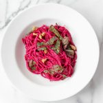 Pasta with beet sauce in white bowl