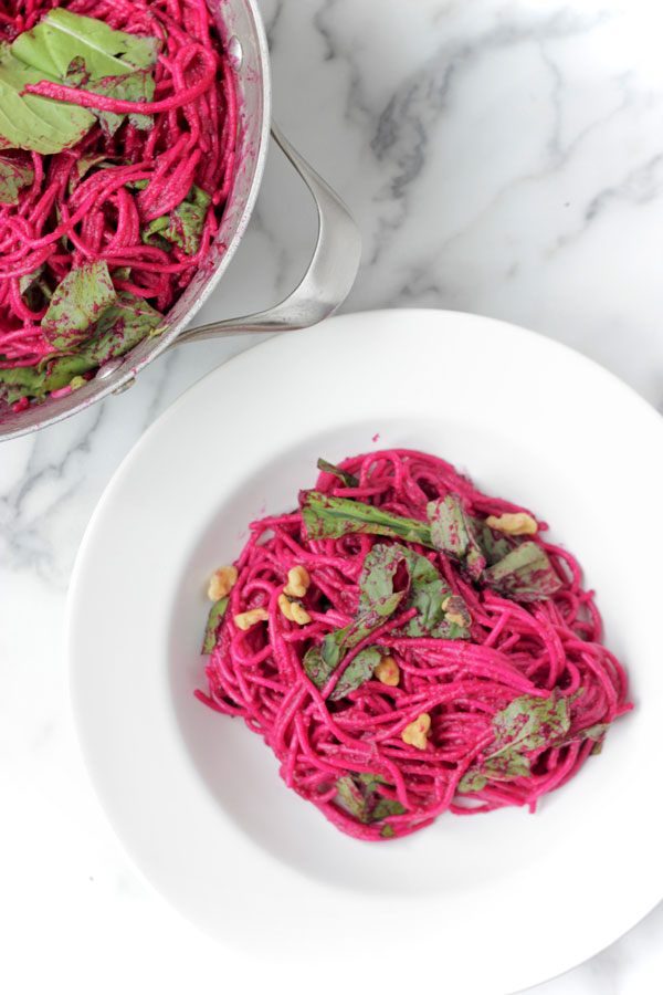 Beet pasta in a white bowl and pot